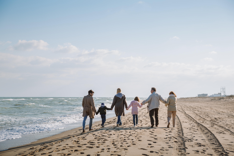 Family en naasten lopen met elkaar over het strand