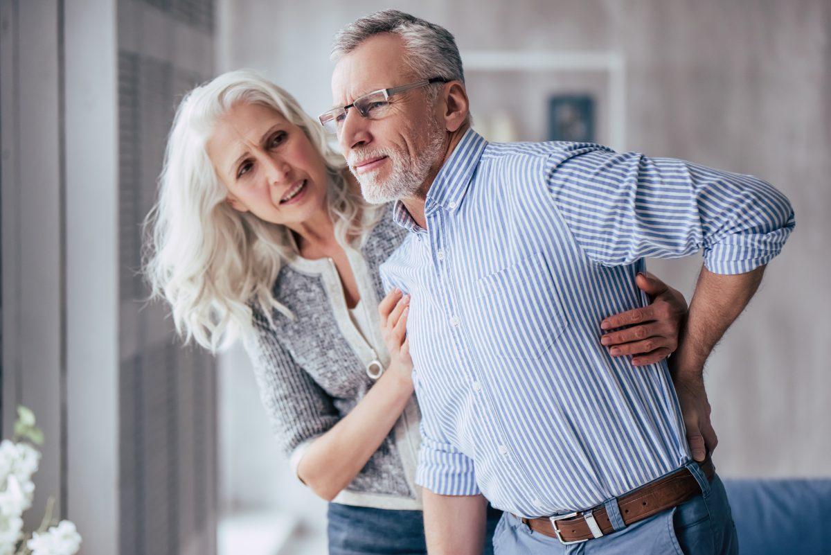 vrouw ondersteunt man met pijnklachten