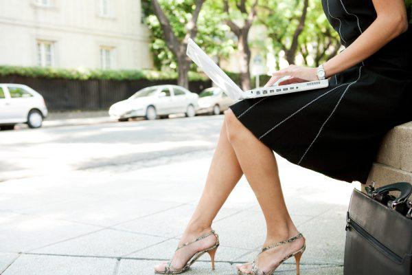 vrouw werkt buiten op haar laptop