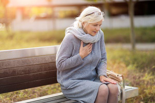 Vrouw zin buiten op een bankje en heeft last van haar hart
