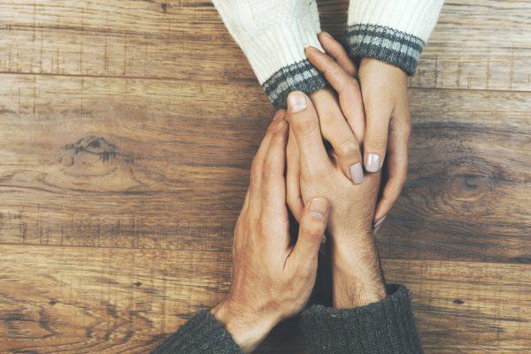 Stel houdt teder elkaars handen vast