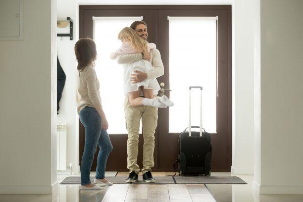 Man knuffelt dochter bij thuiskomst